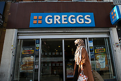 © Licensed to London News Pictures. 05/10/2021. London, UK. A woman walks past a branch of Greggs in north London. Greggs, the bakery chain, warns of price increases of sausage rolls, pasties and steak bakes following the coronavirus and supply chain crises. Photo credit: Dinendra Haria/LNP