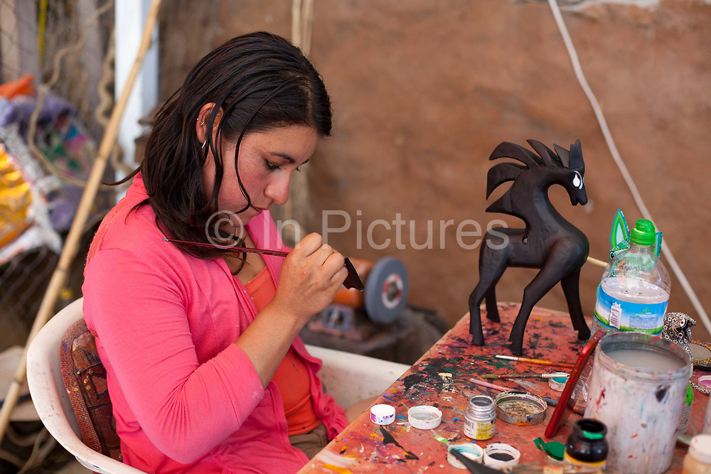 A local artist painting wooden sculptures. Oaxaca in southern Mexico is known for its artisan communities, with each valley having a different specialism - weaving, pottery, wood carving.