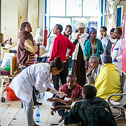 INDIVIDUAL(S) PHOTOGRAPHED: N/A. LOCATION: Felege Hiwot Referral Hospital, Bahir Dar, Ethiopia. CAPTION: Doctors treat patients in the emergency waiting room while others wait their turn.