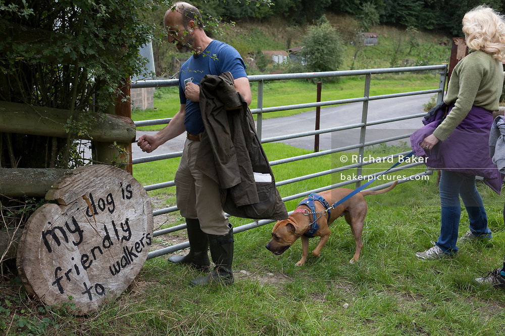 Country walkers pass through a gate with their dog, next to a sign reassuring those entering a field that a pet nearby is walker-friendly, on 10th September 2018, near Lingen, Herefordshire, England UK.