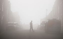 © Licensed to London News Pictures.02/11/15<br /> Saltburn, UK. <br /> <br /> A man walks across a street in Saltburn has heavy fog shrouds the town.<br /> <br /> Photo credit : Ian Forsyth/LNP