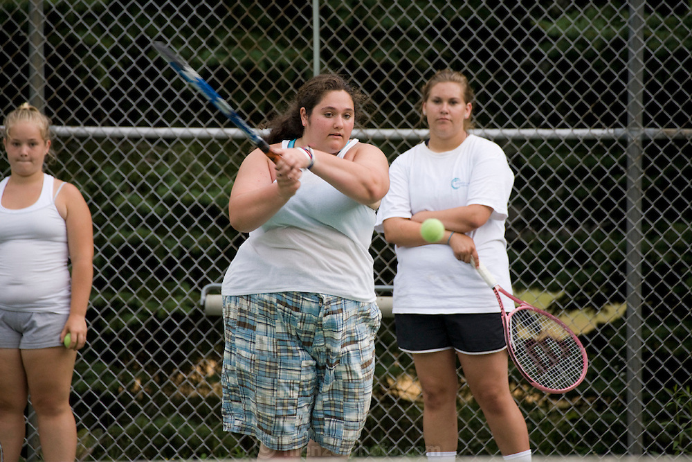 Mackenzie Wolfson plays tennis with her counterparts during a weight loss program at Camp Shane Catskill Mountains, New York. (MacKenzie Wolfson is featured in the What I Eat: Around the World in 80 Diets.)  There are about 500 male and female campers housed in small cabins on shaded hillsides overlooking athletic fields, a small lake, and the camp's most important building, the cafeteria.