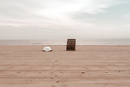 The beach is empty first thing in the morning except for a lifeboat and lifeguard chair