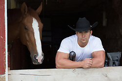 rugged cowboy in a barn with a horse