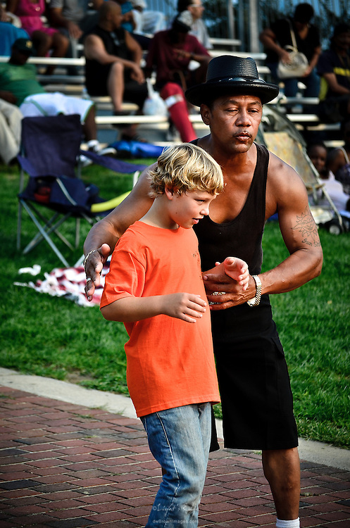 A quick lesson in rhythm and hearing the beat is passed along to a youngster at Wiggins Park's Labor Day weekend concert.