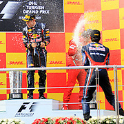 Red Bull Formula One driver Sebastian Vettel of Germany (L) celebrates with the trophy on the podium as team mate Mark Webber of Australia (F) and Ferrari Formula One driver Fernando Alonso of Spain (B) watch, after he won the Turkish F1 Grand Prix at the Istanbul Park circuit in Istanbul May 8, 2011. Photo by TURKPIX