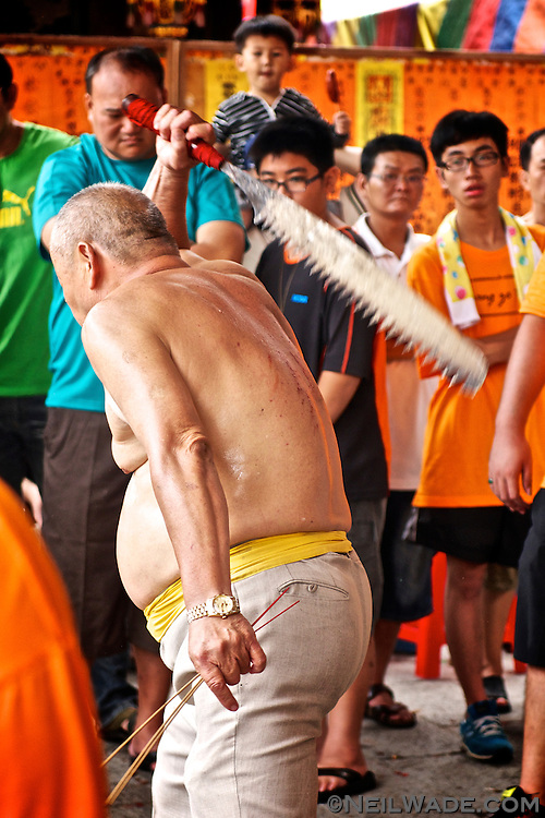 This man is performing a Ji Tong ritual.  The spirit-medium, said to be possessed by the spirit of a Taoist God, self-flagellates using a spiked sword at a religious ceremony in Tainan, Taiwan.