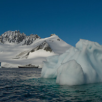 A weathered iceberg drifts in the Neumayer Channel near the Antarctic Peninsula, Antarctica. The National Geographic Endeavor is anchored in the background, adjacent to Wiencke Island.