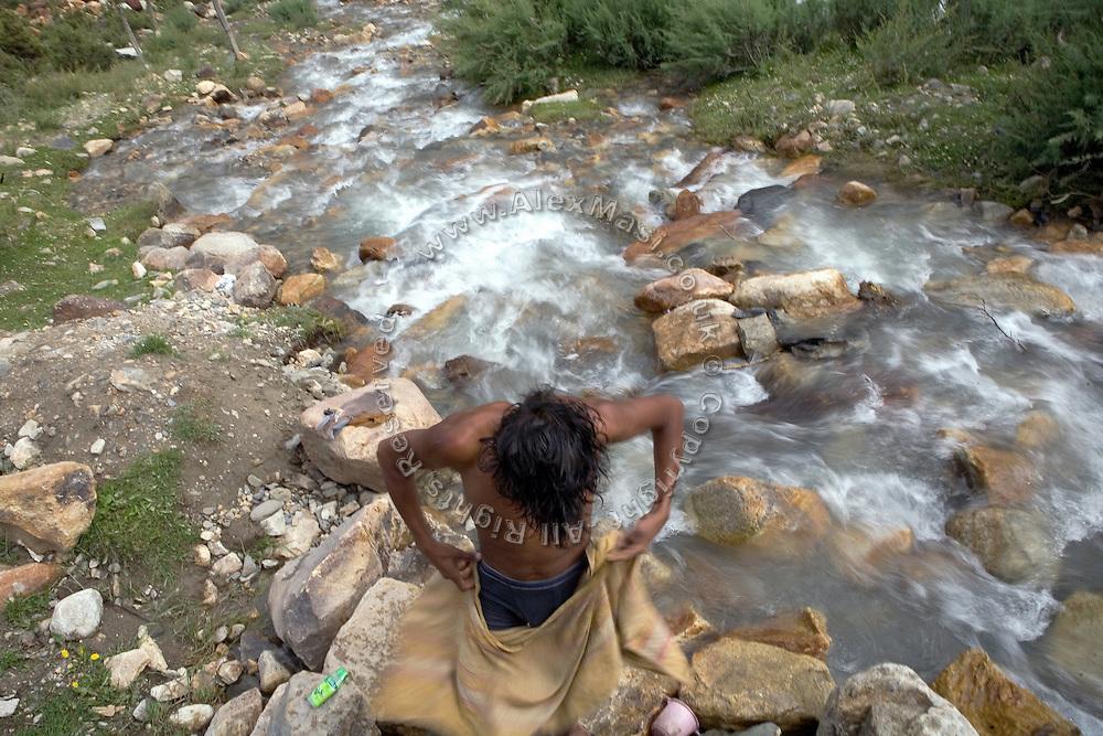 A labourer is having a bath near a little mountain spring along the Leh-Manali Highway.