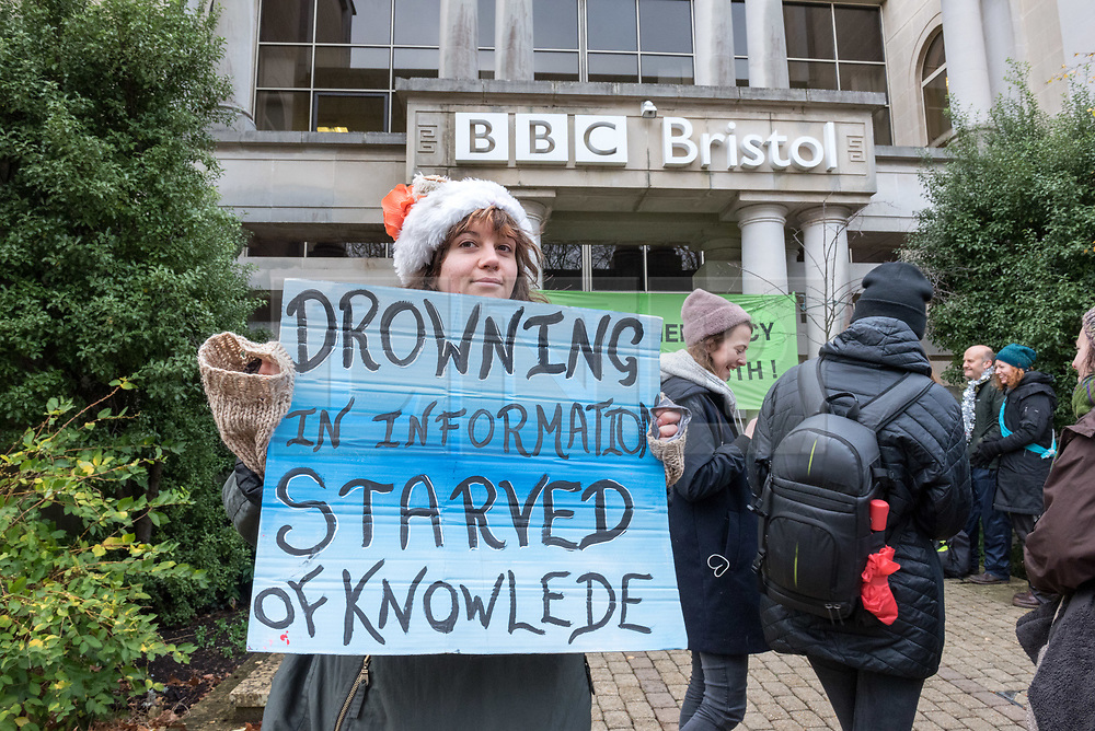 © Licensed to London News Pictures. 21/12/2018. Bristol, UK. 'Extinction Rebellion' campaign event at the BBC Bristol offices in Whiteladies Road where three campaigners locked themselves together blocking the main entrance while others sang modified christmas carols on the shortest day just before Christmas to draw attention to the catastrophic impact of climate change. The Extinction Rebellion campaign says there will be mass actions outside the main BBC headquarters in London, Manchester, Norwich and Bristol to bring to light what they say is the utter failure of the BBC to fulfill their most fundamental duty to educate and inform the British public on the most important issue of our time, the climate crisis.<br /> Extinction Rebellion say the BBC must lead from the front on the climate emergency and make these demands: 1: The BBC Director General Tony Hall to agree to a meeting with a delegation from Extinction Rebellion to discuss how the corporation can meet its crucial moral duty to tell the full truth on the climate and ecological emergency. 2: The BBC to declare a climate and ecological emergency that we need to act now, the extinction of the natural world is happening and we face the collapse of our civilisations.3: That the BBC place the climate and ecological emergency as its top editorial and corporate priority - integrated into all of aspects of the BBC's output, not just environmental sections - by adoption of a climate emergency strategic plan, at the level of urgency the corporation placed on informing the public about World War 2. 4: The BBC to divest all pension funds, investments and bank accounts from fossil fuel corporations and their bankers. 5: The BBC, its subsidiaries and its supply chain to agree to be zero-carbon by 2025. 6: The BBC to publish an annual eco-audit of all BBC operations, including summary of key ecological and carbon data. 7: The BBC to take a lead on encouraging other national & global media corporations to join the global