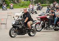 "Russ Holliday with ""Opie"" riding shotgun heads out for the 13th annual Brenda's Ride with Friends from Faro Italian Grille Saturday morning.  Proceeds to benefit the LRGHealthcare Oncology Department.  (Karen Bobotas/for the Laconia Daily Sun)"