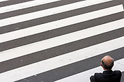 An older, balding salaryman or male office worker waits to cross a road in Tokyo, Japan. March 16th 2012