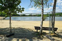© Licensed to London News Pictures. 01/06/2020. LONDON, UK.  The empty beach, seen behind a fence, at Ruislip Lido in north west London.  Hillingdon Council has closed the beach to the public following several days where the public were not adhering to social distancing as coronavirus pandemic lockdown restrictions have been eased by the UK government.  On the first day of the meteorological summer, visitors who travelled from out of the area resorted to finding a place to sunbathe on any patch of grass they could find.  Photo credit: Stephen Chung/LNP