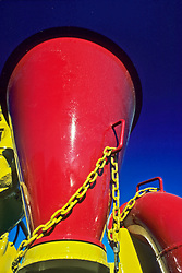 Detail of red fracking equipment with a bright yellow chain against a blue sky background.