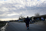 A man carries a tire down the street back to his tornado damaged house in Moore, Oklahoma May 21, 2013. He found the tire several blocks away. A massive tornado tore through a suburb of Oklahoma City, wiping out whole blocks and killing at least 24.   REUTERS/Rick Wilking (UNITED STATES)
