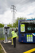 A Nottingham Community Transport bus driver unplugging in one of the Ecolink zero emissions buses to charge in Nottingham, Nottinghamshire, United Kingdom.