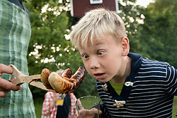 Young boy looking at grilled sausages hungry