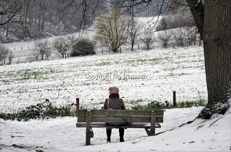 Nederland, Ubbergen, 24-1-2019 De eerste sneeuw van deze winter is gevallen. Een vrouw zit op een bankje wat uitkijkt over   de Elysese velden .Foto: Flip Franssen