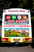 Back  of an ice cream van. Signs on the rear say Piccadilly Whip, Hot Dogs and Caution Children.