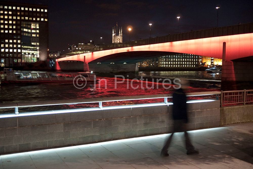 Boats pass at night under London Bridge which in the evening is lit up red. This is one of the most used crossings of the river Thames.