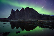 The Aurora Borealis glows in the night sky above the high cliffs of Bear Islands, Scoresby Sund, Greenland