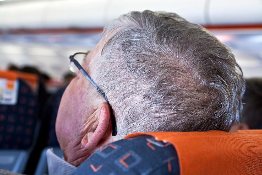 senior man in an airplane resting