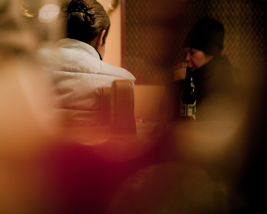2 female friends in a bar drinking beer