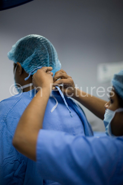 A surgeon has his mask tied by a nurse before an operation in the Medicity, Gurgaon, India<br /> <br /> The Medanta Medicity is India's newest and most comprehensive hospital which when finished, will have 45 operating theatres, 1250 beds and over 350 critical care beds. Uniquely for India, the Institute offers multiple specialisms within one hospital with state of the art treatment facilities.