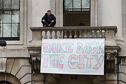 "© Licensed to London News Pictures. 30/12/2015. London, UK. A squatter sits on the balcony of the Royal Mint building with a banner saying ""Take back the city"". Squatters have occupied the former Royal Mint building, located opposite the Tower of London on the border of the City of London to protest against homelessness and highlight how empty buildings could provide shelter for rough sleepers. The site was previously used to manufacture British coins but is currently vacant and activists argue that this along with other vacant commercial buildings could be used to provide short term shelter for the homeless. Photo credit : Vickie Flores/LNP"
