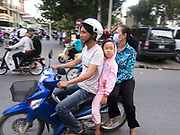 Family traveling on a motor bike in Phnom Penh. Mopeds and motor bikes are a popular mode of transport and motor bikes are also used as taxis.
