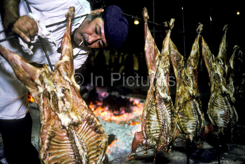 Gaucho cooks sheep and lamb carcasses around a camp fire on ranch, Entre Rios, Argentina