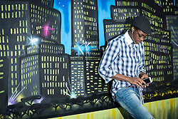 University student listening to music on mobile phone in front of night skyline graffiti wall School, Bavaria, Germany