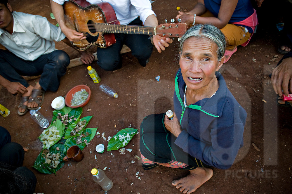 Ethnic Jarai people gather and have some meal arranged on leaves. One man is playing guitar and an old woman looks up. Pleiku area, Vietnam, Asia