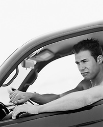 Man sitting inside a car without a shirt