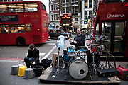 Drummer Oded Kafri, running a project called 'the DruMachine' and partner playing on buckets busk outside Liverpool Street Station in rush hour. This is busking on a grand scale in one of London's busiest commuter stations.