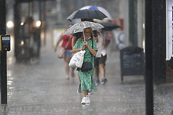 © Licensed to London News Pictures. 13/08/2020. Epsom, UK. Shoppers run for cover in Epsom, Surrey as the UK experiences thunderstorms and heavy rainfall following days of high temperatures. Photo credit: Peter Macdiarmid/LNP