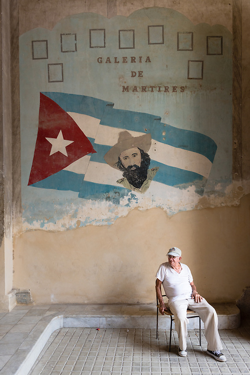 Man sitting in front of tribute to heroes of the Cuban revolution painted on a wall in a Havana apartment building