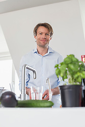 Portrait of mature man standing in kitchen, smiling