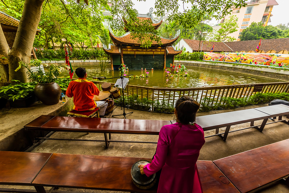 Musicians, Traditional water puppet show at the Performing Arts Revival Theatre at the Vietnam Museum of Ethnology. Vietnamese water puppetry was originated in the villages of the Red River Delta area of northern Vietnam a thousand years ago.  A Water Puppet Show is the unique art performed in a pool of water with the water surface being the stage. The puppeteers control the puppets with long bamboo rods behind a split-bamboo screen. A traditional Vietnamese orchestra provides background music accompaniment. Hanoi, northern Vietnam.