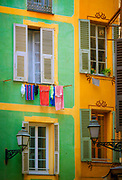 """Typical French windows in the """"Vielle Ville"""" part of Nice, France<br /> .....<br /> Nice is the fifth most populous city in France, after Paris, Marseille, Lyon and Toulouse, and it is the capital of the Alpes Maritimes département. The urban area of Nice extends beyond the administrative city limits with a population of about 1 million on an area of 278 sq mi. Located on the south east coast of France on the Mediterranean Sea, Nice is the second-largest French city on the Mediterranean coast and the second-largest city in the Provence-Alpes-Côte d'Azur region after Marseille.<br /> <br /> The city is called Nice la Belle, which means Nice the Beautiful, which is also the title of the unofficial anthem of Nice, written by Menica Rondelly in 1912. The area of today's Nice contains Terra Amata, an archaeological site which displays evidence of a very early use of fire. Around 350 BC, Greeks of Marseille founded a permanent settlement and called it Nikaia, after Nike, the goddess of victory. Through the ages, the town has changed hands many times. Its strategic location and port significantly contributed to its maritime strength. For years it was a dominion of Savoy, then became part of France between 1792 and 1815, when it was returned to Piedmont-Sardinia until its reannexation by France in 1860.<br /> <br /> The natural beauty of the Nice area and its mild Mediterranean climate came to the attention of the English upper classes in the second half of the 18th century, when an increasing number of aristocratic families took to spending their winter there. The city's main seaside promenade, the Promenade des Anglais ('the Walkway of the English') owes its name to the earliest visitors to the resort. For decades now, the picturesque Nicean surroundings have attracted not only those in search of relaxation, but also those seeking inspiration. The clear air and soft light has been of particular appeal to some of Western culture's most outstanding painters, such as Marc Ch"""