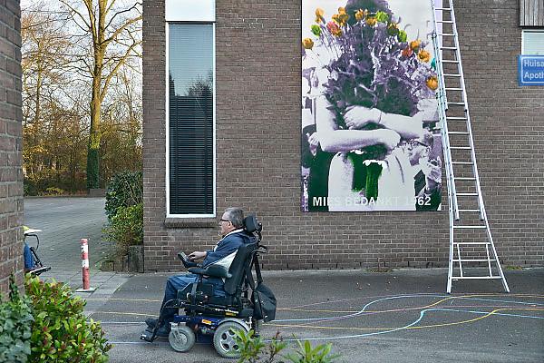Nederland, Arnhem, het dorp,  22-11-2012Een man in een scootmobiel rijdt lang een poster met daarop Mies Bouwman die bloemen krijgt tijdens de actie in 1962 Open Het Dorp.Foto: Flip Franssen