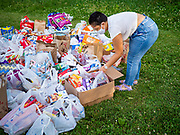 25 JUNE 2020 - DES MOINES, IOWA: A Black Lives Matter supporter sorts groceries for the homeless donated to BLM. Nearly 100 volunteers came to a community support event organized by Black Lives Matter in Good Park in Des Moines. They sorted supplies donated to BLM, including food, sanitary supplies, first aid supplies, batteries, blankets, tents, and bottled water. The emergency packages will be distributed to homeless people in Des Moines.        PHOTO BY JACK KURTZ