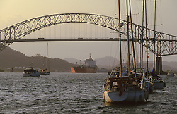 Bridge of the Americas or Puentes de las Americas spans the Panama Canal (Canal de Panama) entrance to the Pacific Ocean.  Moored sailboats line the harbor at dusk.