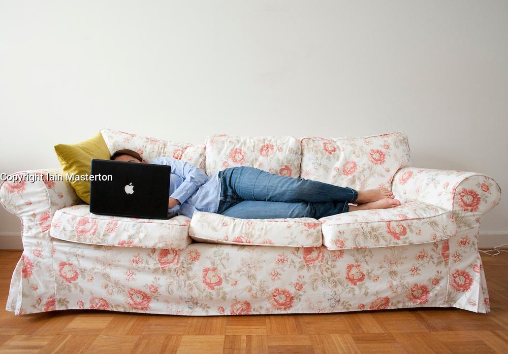Woman lying on sofa using a laptop computer