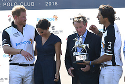 Nacho Figures presents the trophy with Meghan, Duchess of Sussex, wearing a navy blue dress by Carolina Herrera,  Prince Harry, Duke of Sussex and Enda Kenny following the Sentebale ISPS Handa Polo at the Royal County of Berkshire Polo Club on July 26, 2018.