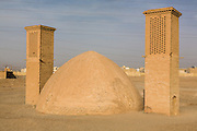 Wind towers (Badgir) next to a building which acts as a refrigerator to store food , Yazd, Iran