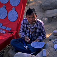 Asia, Nepal, Kathmandu, Swayambhunath Stupa. A Nepalese slate carver creates Buddhist souvenirs along the steps to Swayambhunath.