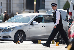 © Licensed to London News Pictures. 13/04/2019. London, UK. A police officers passes a car with a smashed window in Holland Park after shots were fired by police near the Ukranian embassy. Photo credit: Peter Macdiarmid/LNP