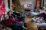 A British family watch the Queens speech to the nation on Christmas Day, a tradition started in 1932 and which she first broadcast on television in 1957, on 25th December 2019, in Bristol, England.