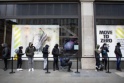 © Licensed to London News Pictures. 12/04/2021. London, UK. A shopper sits in a queue outside Niketown shop on Oxford Street . From today gyms, non essential retail and theme parks can reopen following the easing of lockdown restrictions. Photo credit: George Cracknell Wright/LNP